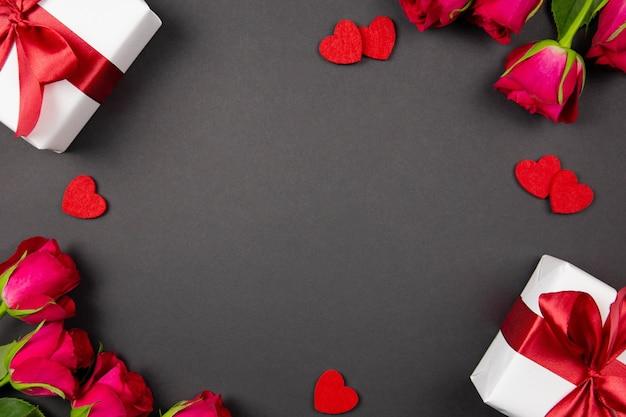 Flaches laienkonzept von valentinstag, jahrestag, muttertag und geburtstagsgruß mit geschenkboxen schönes rotes band, herzen und rosen auf dunkelheit.