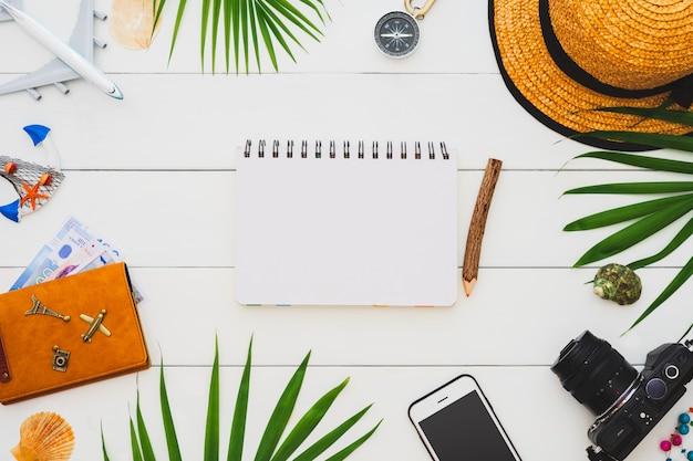 Flaches laienreisendzubehör mit leerem notizbuch