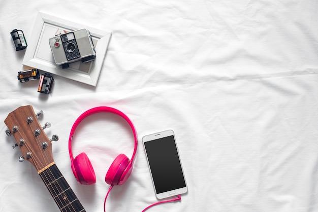 Flaches lay-lebensstil-konzept mit smartphone, kopfhörer, kamera auf weißem gewebe-hintergrund