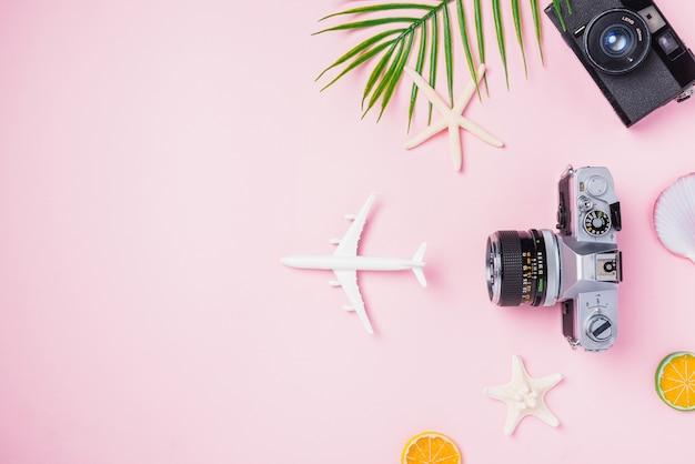 Flaches lay-mockup von retro-kamerafilmen, flugzeug-seestern-hut und tropischem zubehör für reisende