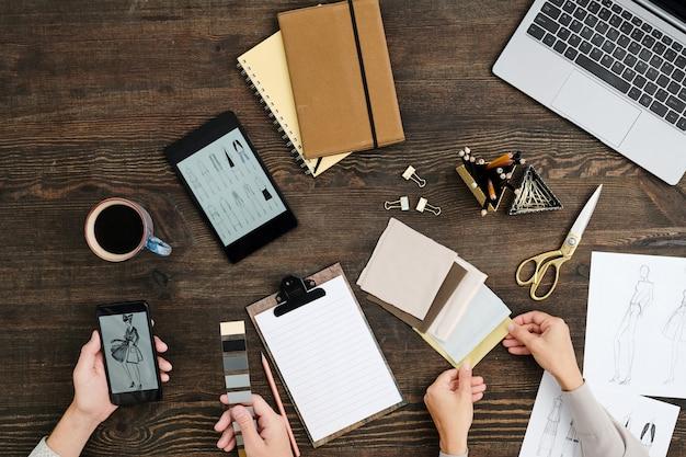 Flaches layout der hände zeitgenössischer kreativer modedesigner, die am holztisch sitzen und stoffmuster für neue kollegen auswählen
