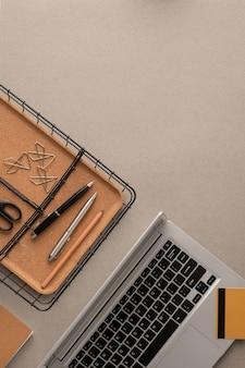 Flaches layout der kreditkarte über der laptop-tastatur, korb mit zwei stiften und bleistift, mehrere clips und schere mit kopienraum für text auf der rechten seite