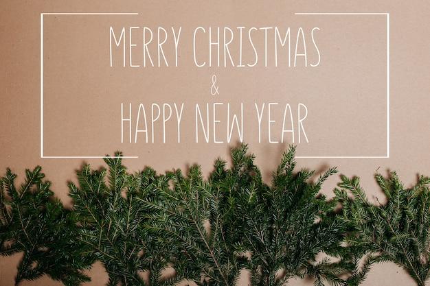 Flaches layout der weihnachtsdekoration mit platz für text. tannenzweige auf dem kartonhintergrund. umweltfreundliche weihnachtsschmuck. skandinavische weihnachtskarten.