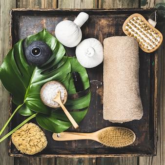 Flaches layout mit monstera-blättern und kosmetischen pflegeprodukten