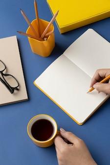 Flaches notizbuch mit aufgabenliste auf dem schreibtisch mit einer tasse kaffee daneben