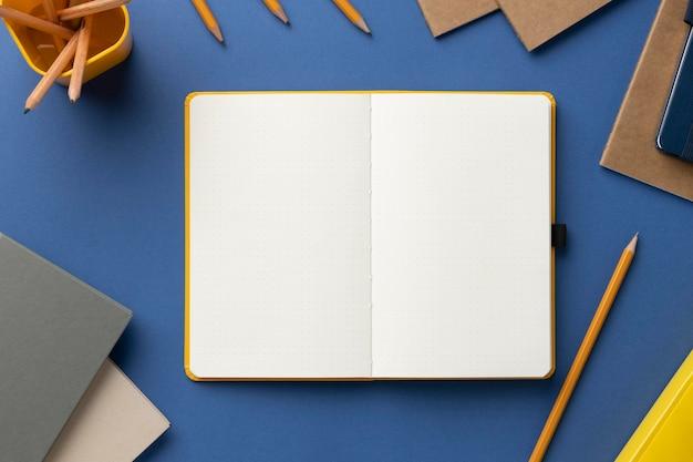 Flaches notizbuch mit aufgabenliste auf dem schreibtisch