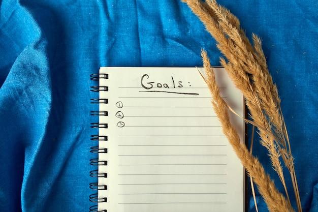 Flaches notizbuch mit draufsicht, notizen mit pampasgras auf tischdeckenhintergrund, lebensziele und plan