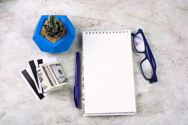 Flaches notizbuch mit leerem weißem blatt, stift, geld, kreditkarten, gläsern und succulent