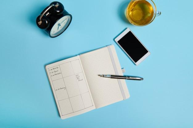 Flaches offenes notizbuch mit zeitplan, smartphone, tintenstift, glastasse tee und schwarzer wecker liegen auf blauer oberfläche. farbhintergrund mit kopienraum. zeitmanagement, deadline, terminkonzept