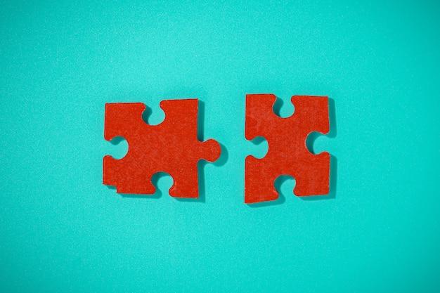 Flaches puzzle mit zwei roten teilen auf blauem tisch