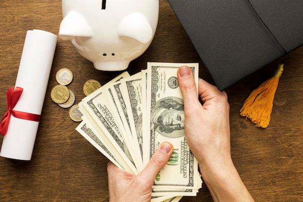 Flaches sparschwein mit akademischer kappe und banknoten