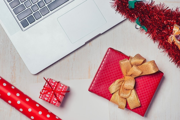 Flaches weihnachtsgeschenk mit laptop über weißem holzhintergrund