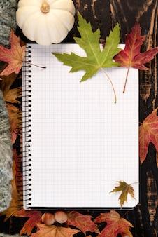 Flaches weißes notizbuch mit eicheln und herbstlaub auf holztisch. herbststillleben. gemütliche herbststimmung. platz kopieren.