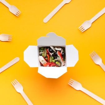 Flachkiste mit salat und geschirr