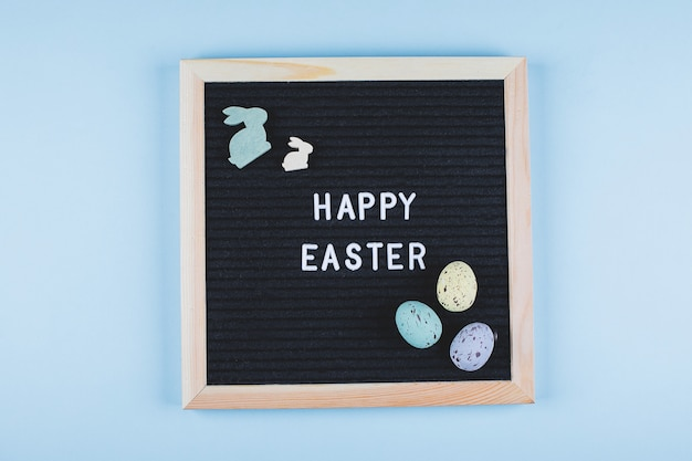 Flachkonzept der osterkarte. grußbrett mit text frohe ostern und bunte pastell-eier, hölzernes häschen auf blauem hintergrund. draufsicht.