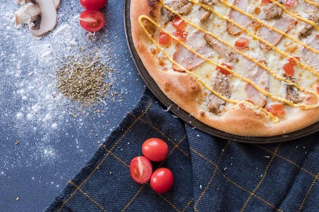 Flachlage mit traditioneller italienischer pizza mit chiken auf dunkelblauer steintabelle