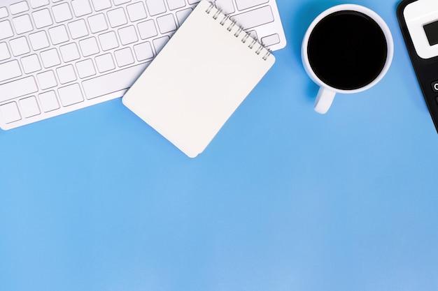 Flachlegen schreibtisch schreibtisch des modernen arbeitsplatzes mit laptop auf blauem tisch, draufsicht laptop