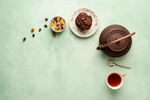 Flachlegerahmen mit teekanne und muffin