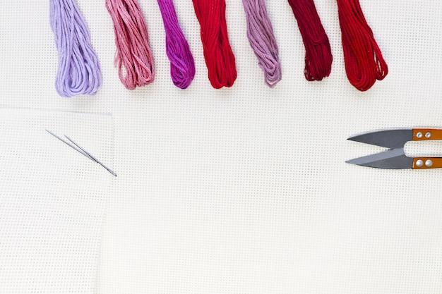 Flachliegende draufsicht mit einer stickleinwand, nadeln und roten fäden