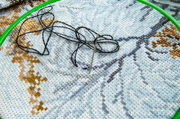 Flachliegende leinwand mit einem schönen muster aus hellen nähfäden und einer nadel für die stickerei-nahaufnahme