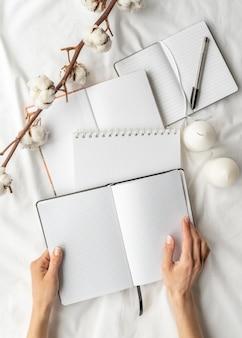 Flachliegende notizbücher und baumwollarrangement