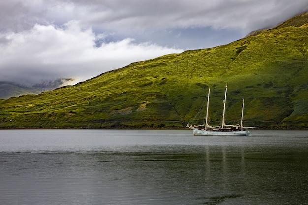 Flachwinkelaufnahme eines einzelnen schoners im killary harbour, galway, republik irland