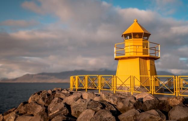 Flachwinkelaufnahme eines gelben leuchtturms, aufgenommen an einem bewölkten tag