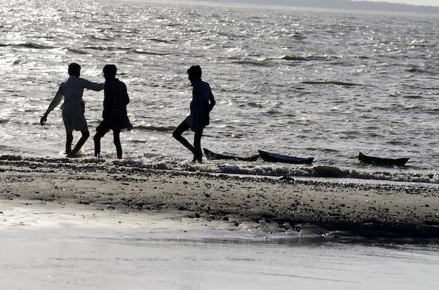 Flachwinkelaufnahme von leuten, die am strand spazieren gehen