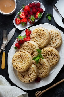 Fladen mit beeren zum frühstück. deliciouse traditionelle englische pfannkuchen, aufläufe am morgen serviert.