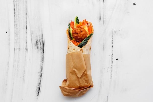 Fladenbrot mit falafel und gemüse auf einem weißen tisch