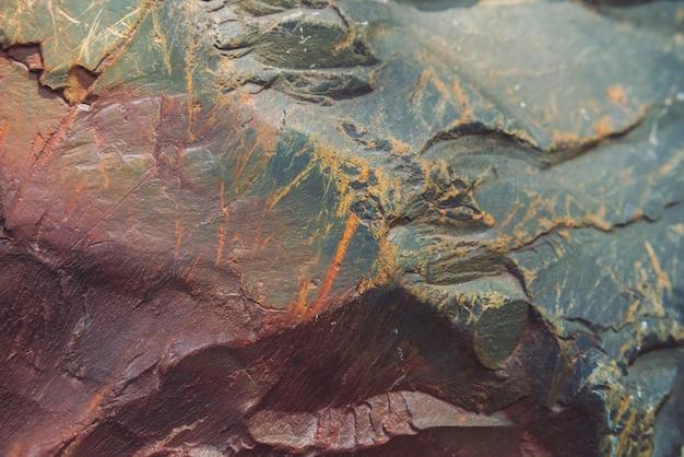 Fläche des mehrfarbigen flusssteins im makro. schöner felsenoberflächenabschluß oben. bunter strukturierter stein. erstaunlicher ausführlicher hintergrund des hochlandflusssteins mit moosen und flechten. natürliche beschaffenheit des berges.