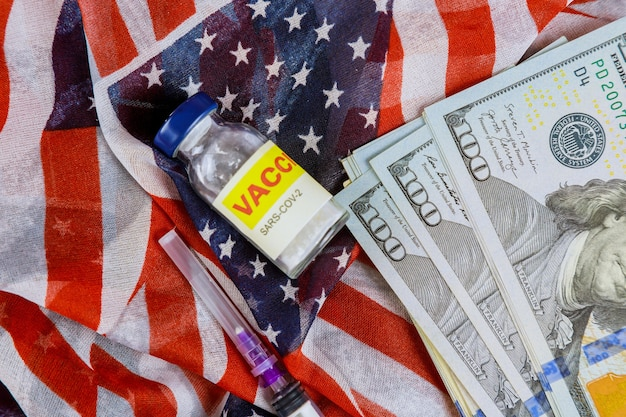 Fläschchen glasflasche des amerikanischen impfstoffs sars-cov-2, covid-19 coronavirus mit dollar viele us-rechnungen die usa-flagge im hintergrund