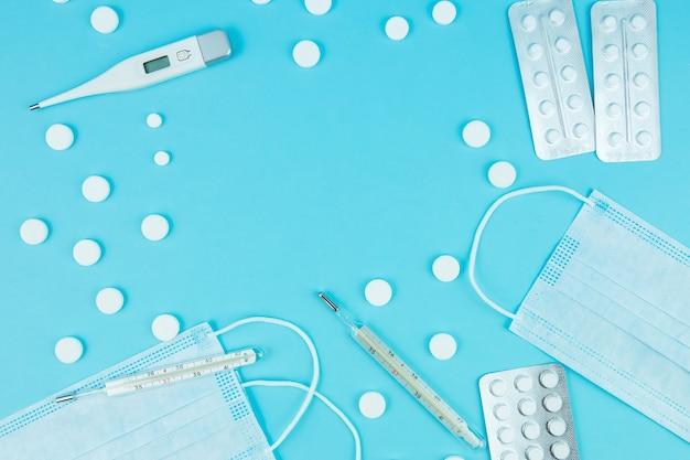 Fläschchen mit medikamenten, pillen, spritzen, thermometer, medizinischer maske auf einem blauen tisch. ein heilmittel gegen saisonale grippe und erkältung. mittel zur behandlung von covid-19. platz für text. coronavirus
