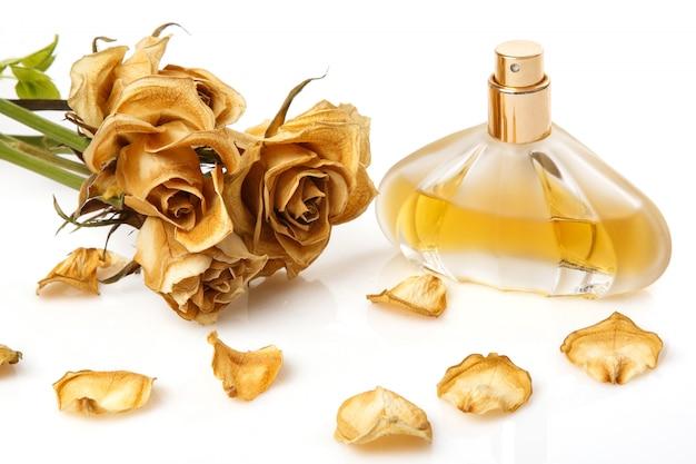 Fläschchen mit parfüm und trockener rosenblüte