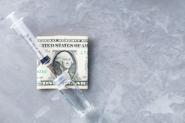 Fläschchen mit spritzenimpfstoff und einem dollar auf grauem hintergrund