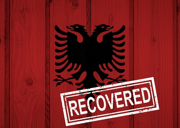 Flagge albaniens, die die infektionen der corona-virus-epidemie oder des coronavirus überlebt oder sich davon erholt hat. grunge-flagge mit stempel wiederhergestellt