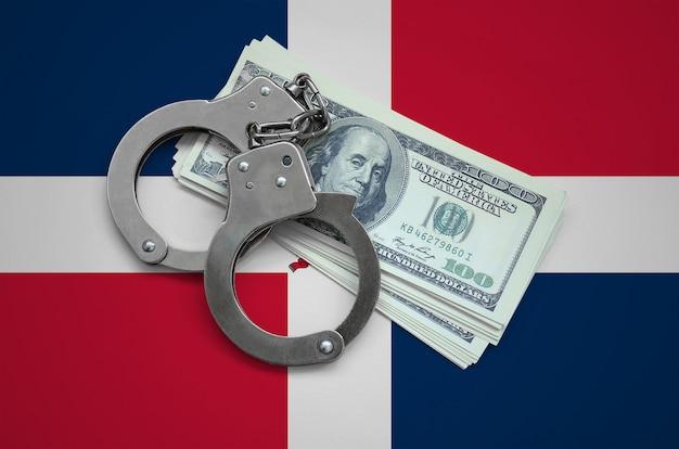 Flagge der dominikanischen republik mit handschellen und einem bündel dollar. währungskorruption im land. finanzielle verbrechen