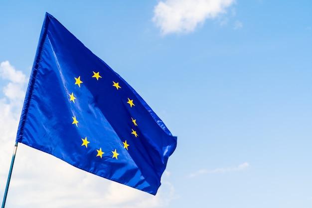 Flagge der europäischen union gegen das wellenartig bewegen des blauen himmels