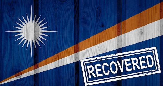 Flagge der marshallinseln, die die infektionen der coronavirus-epidemie oder des coronavirus überlebt oder sich davon erholt haben. grunge-flagge mit stempel wiederhergestellt