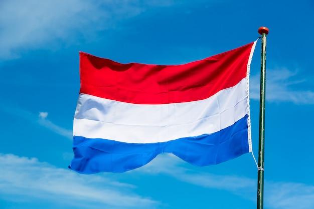 Flagge der niederlande, die in den wind gegen blauen himmel wellenartig bewegen