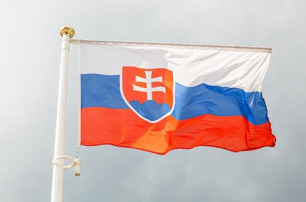 Flagge der slowakei auf fahnenmaterial vor dem himmel
