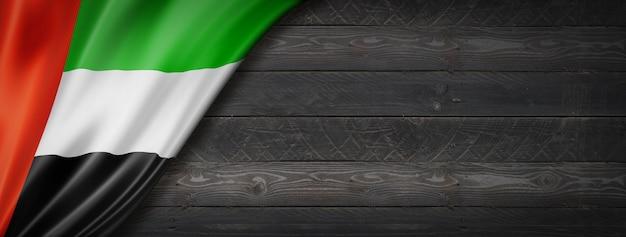 Flagge der vereinigten arabischen emirate auf schwarzer holzwand. panorama.