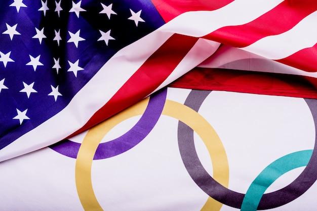 Flagge der vereinigten staaten über eine flagge mit den olympischen ringen gefaltet.