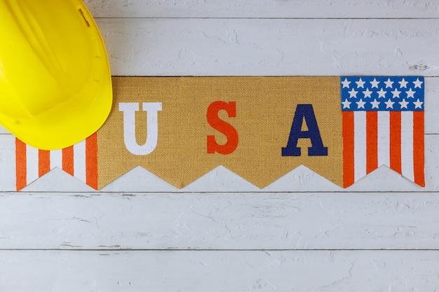 Flagge der vereinigten staaten von amerika happy labour day zeichen auf gelbem helm