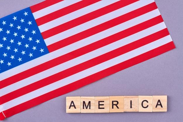 Flagge der vereinigten staaten von amerika. hölzerne alphabetblöcke mit buchstaben lokalisiert auf violettem hintergrund.