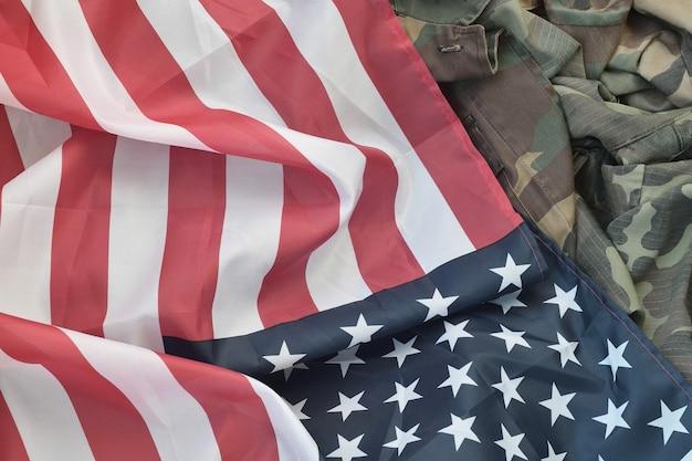 Flagge der vereinigten staaten von amerika und gefaltete militäruniformjacke. militärische symbole
