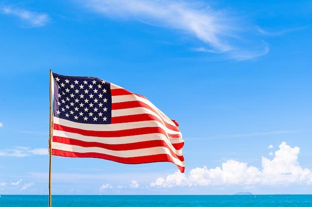 Flagge der vereinigten staaten von amerika (usa), die im wind mit blauem himmel und wolke an einem sonnigen tag winken