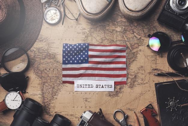 Flagge der vereinigten staaten von amerika zwischen dem zubehör des reisenden auf alter weinlese-karte. obenliegender schuss
