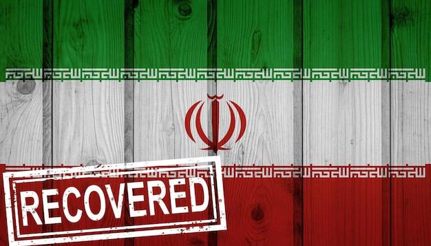 Flagge des iran, die die infektionen der corona-virus-epidemie oder des coronavirus überlebt oder sich davon erholt hat. grunge-flagge mit stempel wiederhergestellt