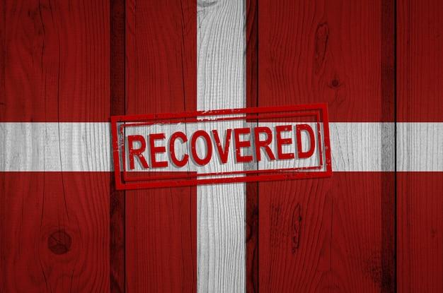 Flagge des johanniterordens, die die infektionen der corona-virus-epidemie oder des coronavirus überlebt oder sich davon erholt hat. grunge-flagge mit stempel wiederhergestellt